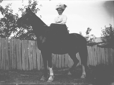 A woman on horseback. A paling fence and house are in the background.
