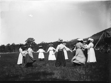 A group of women holding hands in a circle. All are wearing long dresses and hats.