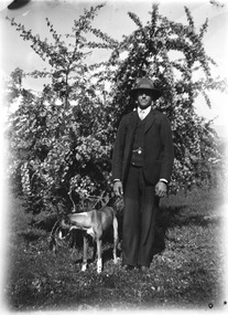 A man and his dog. He is wearing a three piece suit and a hat. There is a tree in the background.