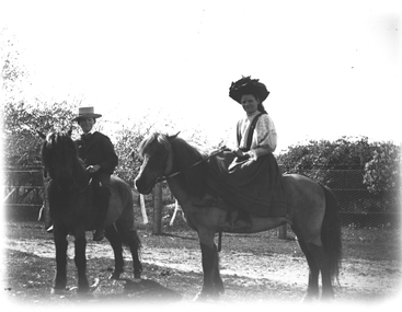 Boy and girl astride their ponies. The girl is seated side-saddle.