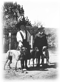 A girl and boy with 3 dogs. There is a wooden picket fence in the background.