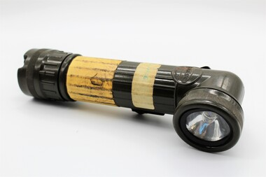 Army issued battery powered torch; olive drab in colour with beacon at right-angle to trunk.