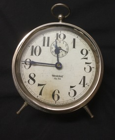 """Clock with round white dial and black numerals. """"Westclox"""" inscribed on dial."""