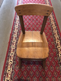 A small lacquered wooden  kindergarten chair with a seat, backrest, four legs and two side supports for the backrest.