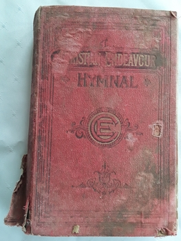 The red cloth badly damaged hymnal has black and gold faded lettering of title and symbol of E surrounded by a circle on the front cover.