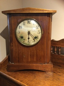 Plain wooden mantle clock with a ceramic dial, black digits and hands. Has a glass cover that opens.