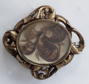 A swirled patterned highly decorated brass brooch with human hair under a glass cover.