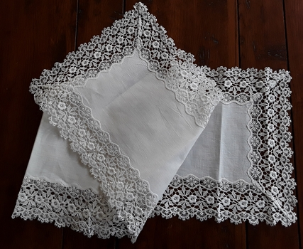 A long white floral patterned lace embroidered edged cotton table runner for a table or sideboard.