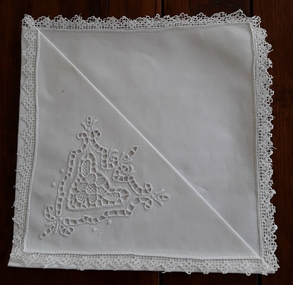Seven white square Richelieu cutwork cotton serviettes with Filet Lace borders for use when dining.