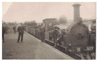 Postcard of men standing on platform beside steam engine R327 at Linton Railway station and two young men sitting on the side front platform.