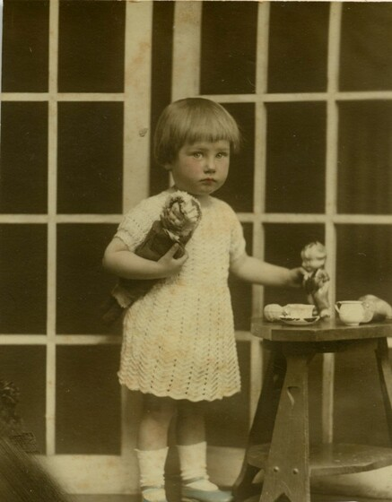 a child in white lace dress stands next to table and tea set, holding two dolls