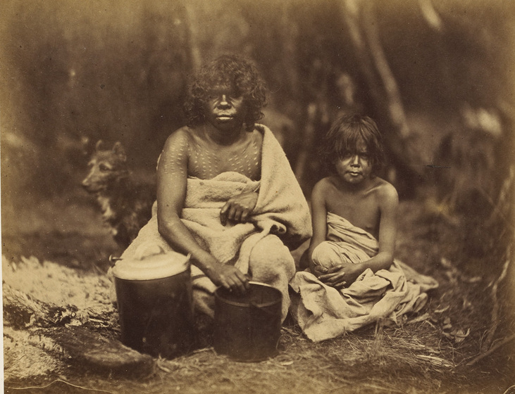 An early photograph, sepia with age, of a woman and child wrapped in blankets sitting beside a fire and holding two billy cans with a dog in the background.