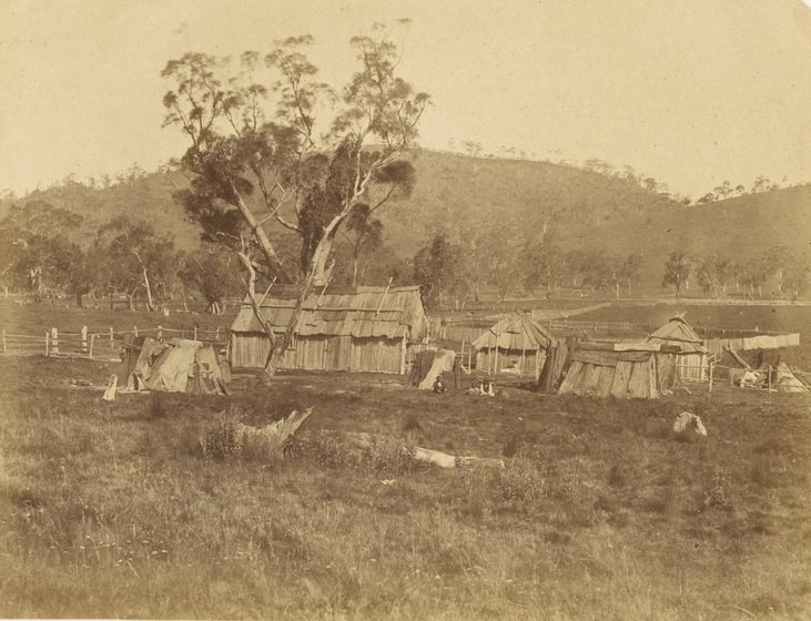 An early photograph, sepia with age, featuring a cluster of six old timber buildings in a rural field.