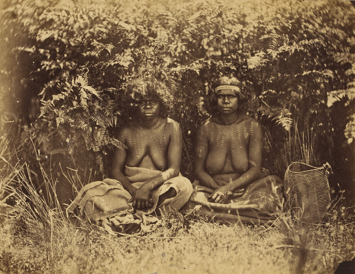 An early photograph, sepia with age, of two women sitting in the shade of bushes with dilly bags beside them on the grass