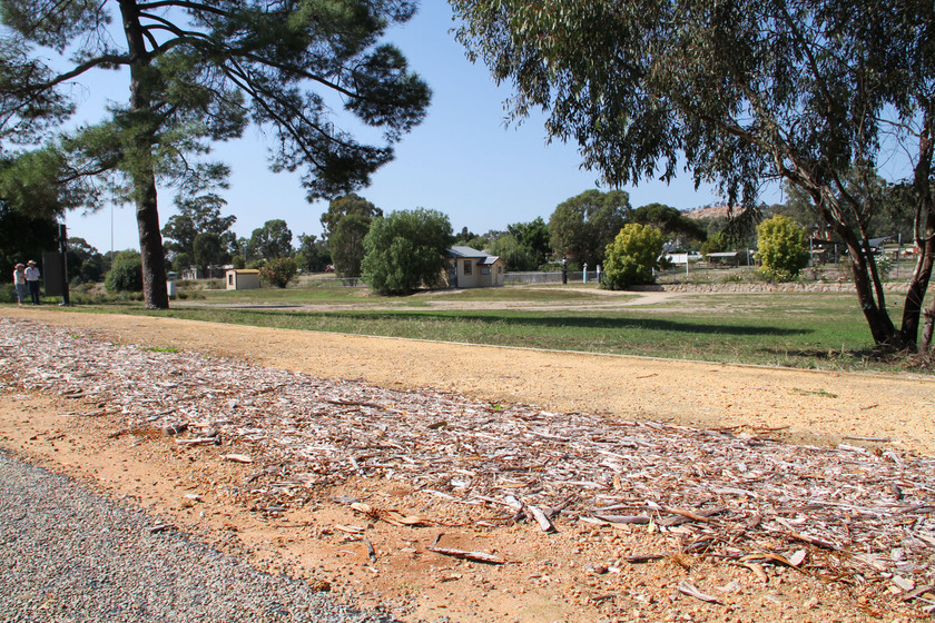 Street side view showing location of Gravel Contractors' Encampment, modern road, footpath in the foreground, small buildings in the distance.