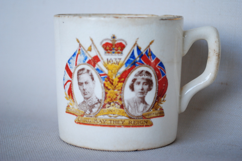 Mug with two portraits with flags seen behind and crown in between