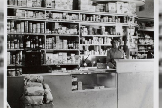 Woman standing in front of shelving in a general store
