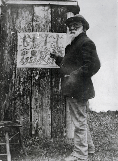 man stands at a hut, as he prepares a painting