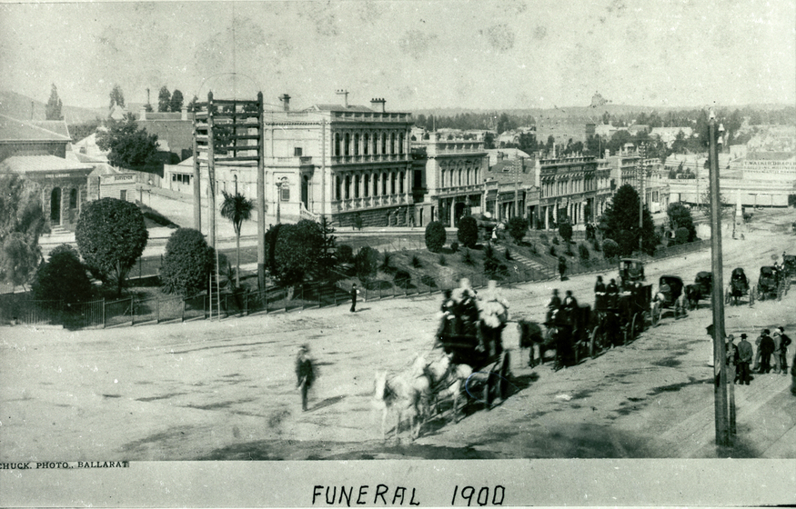 A horse drawn funeral procession and mourners wend their way down the main street