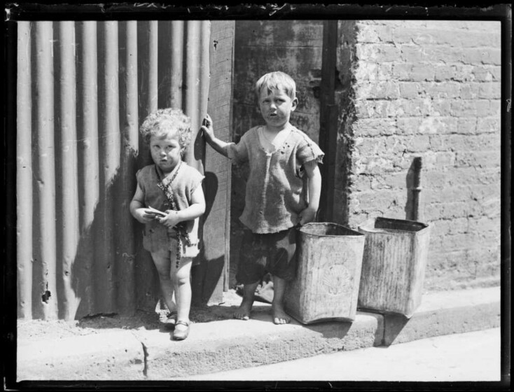 A black and white photograph of two young children in dirty clothing standing on the street.